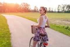 Muchacha con la bici en la puesta del sol del verano en el camino en el parque de la ciudad Rueda del primer del ciclo en fondo b imagen de archivo