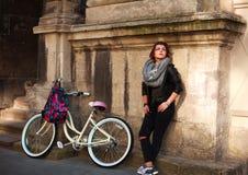 Muchacha con la bicicleta del vintage en el fondo del edificio antiguo de la pared Foto de archivo libre de regalías