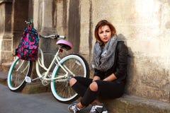 Muchacha con la bicicleta del vintage que se sienta por la pared del edificio antiguo Fotos de archivo libres de regalías