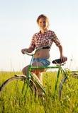 Muchacha con la bicicleta en hierba Foto de archivo