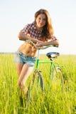 Muchacha con la bicicleta en hierba Fotografía de archivo