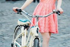 Muchacha con la bicicleta en la calle con la bicicleta retra Imagen de archivo