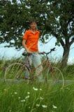 Muchacha con la bicicleta en país Imagenes de archivo