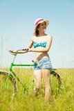 Muchacha con la bicicleta en prado de la hierba Imagen de archivo libre de regalías