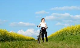Muchacha con la bicicleta en un camino de tierra en campo de la rabina Foto de archivo