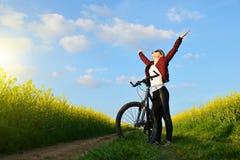Muchacha con la bicicleta en un camino de tierra en campo de la rabina Fotografía de archivo libre de regalías