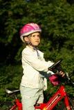 Muchacha con la bicicleta y el casco Fotos de archivo