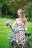 Muchacha con la bicicleta y las flores en campo Imagen de archivo libre de regalías