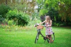 Muchacha con la bicicleta y las flores en campo Foto de archivo libre de regalías