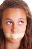 Muchacha con la boca sujetada con cinta adhesiva Imágenes de archivo libres de regalías