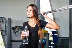 Muchacha con la botella de agua en un gimnasio Fotos de archivo
