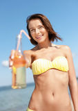 Muchacha con la botella de bebida en la playa Fotografía de archivo libre de regalías