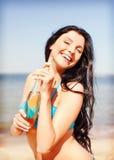 Muchacha con la botella de bebida en la playa Imagenes de archivo