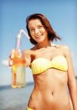 Muchacha con la botella de bebida en la playa Foto de archivo libre de regalías