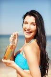 Muchacha con la botella de bebida en la playa Fotos de archivo