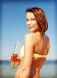Muchacha con la botella de bebida en la playa Fotos de archivo libres de regalías