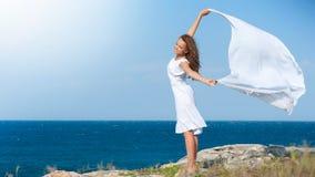 Muchacha con la bufanda blanca en la roca Fotografía de archivo