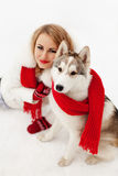 Muchacha con la bufanda roja que se sienta con un husky siberiano en la nieve foto de archivo libre de regalías