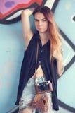 Muchacha con la cámara del vintage contra la pared de la pintada Foto de archivo libre de regalías