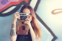 Muchacha con la cámara del vintage contra la pared y las fotografías Foto de archivo libre de regalías