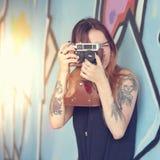 Muchacha con la cámara del vintage contra la pared y las fotografías Fotografía de archivo libre de regalías