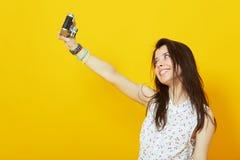 Muchacha con la cámara del vintage que toma a foto el fondo amarillo Imagen de archivo