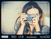 Muchacha con la cámara del vintage vista a través del visor Foto de archivo