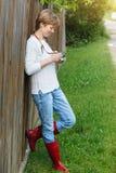 Muchacha con la cámara retra de la foto cerca de la cerca al aire libre Foto de archivo libre de regalías