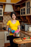 Muchacha con la cacerola que cocina la cena en la cocina Fotos de archivo