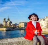 Muchacha con la caja del regalo de Navidad que mira en distancia en París Imagen de archivo