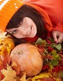 Muchacha con la calabaza en las hojas de otoño. Foto de archivo