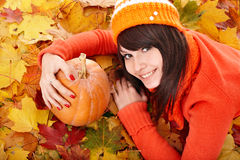 Muchacha con la calabaza en las hojas de otoño. Imágenes de archivo libres de regalías