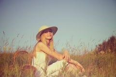 Muchacha con la cesta que se sienta en campo Foto de archivo