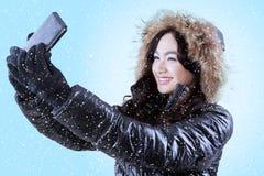 Muchacha con la chaqueta del invierno que toma la imagen Imágenes de archivo libres de regalías