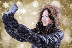 Muchacha con la chaqueta del invierno que toma la imagen del selfie Foto de archivo libre de regalías