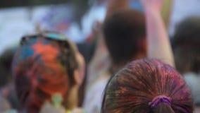 Muchacha con la cola de caballo que baila y que disfruta del fest de Holi, mostrando la muestra del amor con las manos almacen de metraje de vídeo