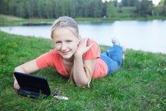 Muchacha con la computadora portátil al aire libre Imagenes de archivo