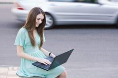 Muchacha con la computadora portátil al aire libre Fotografía de archivo