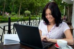 Muchacha con la computadora portátil en café imagenes de archivo