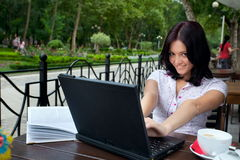 Muchacha con la computadora portátil en café imagen de archivo