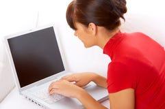 Muchacha con la computadora portátil en el sofá Imagenes de archivo