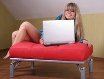 Muchacha con el ordenador portátil en el sofá rojo foto de archivo
