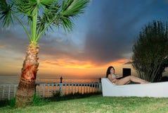 Muchacha con la computadora portátil en la puesta del sol Foto de archivo libre de regalías