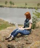Muchacha con la computadora portátil en la roca cerca del lago y del árbol. Fotos de archivo libres de regalías