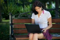 Muchacha con la computadora portátil en parque Imagen de archivo libre de regalías