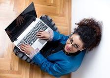 Muchacha con la computadora portátil en suelo Foto de archivo libre de regalías