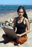 Muchacha con la computadora portátil en una playa Fotografía de archivo libre de regalías