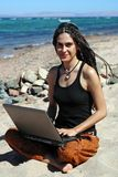Muchacha con la computadora portátil en una playa Fotografía de archivo