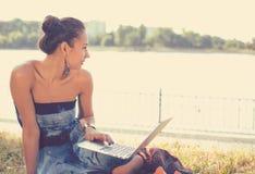Muchacha con la computadora portátil Mujer hermosa con el cuaderno que se sienta en la hierba fotografía de archivo