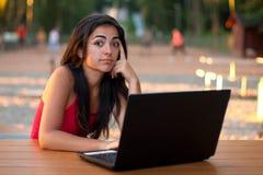 Muchacha con la computadora portátil - pensando Fotos de archivo